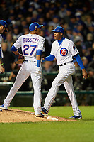 Chicago Cubs pitcher Aroldis Chapman (54) takes the mound as Addison Russell (27) looks to the scoreboard in the seventh inning during Game 5 of the Major League Baseball World Series against the Cleveland Indians on October 30, 2016 at Wrigley Field in Chicago, Illinois.  (Mike Janes/Four Seam Images)
