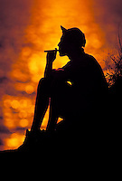 Man in silhouette smoking a cigar.