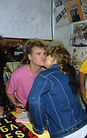 Alan Frew, singer of Glass Tiger get a kiss from a fan at a autographe session in a Montreal record store<br /> Circa 1986- Montreal<br /> Photo : (c)by Pierre Roussel / Images Distribution