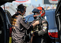 Mar. 15, 2013; Gainesville, FL, USA; A crew member helps NHRA funny car driver Tony Pedregon during qualifying for the Gatornationals at Auto-Plus Raceway at Gainesville. Mandatory Credit: Mark J. Rebilas-