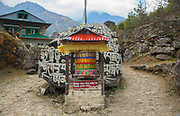 Nachipang Nepal A prayer wheel in front of  Mani Wall in the village of Nachipang, Solukhumbu