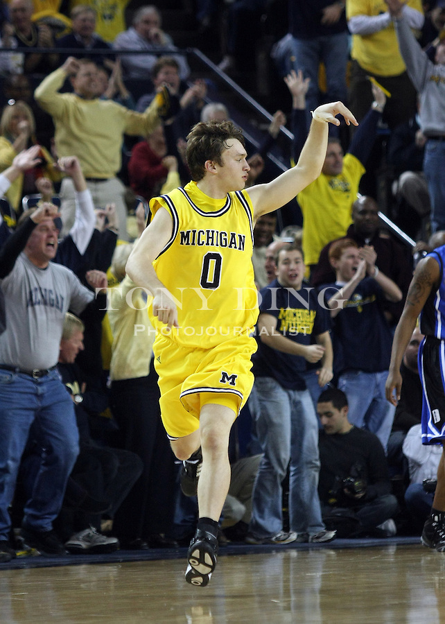 Michigan guard Zack Novak (0) celebrates after scoring a three pointer  in the second half of an NCAA college basketball game with Duke, Saturday, Dec. 6, 2008, in Ann Arbor, Mich. Michigan upset No. 4th ranked Duke 81-73. (AP Photo/Tony Ding)