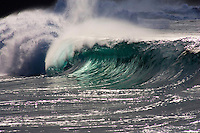 The silhouette of a beautiful large wave by afternoon sun.  Waimea Bay shore break on the North shore of Oahu, Hawaii.
