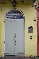 French Quarter, New Orleans, Louisiana.  Pirate's Alley.  William Faulkner House with Yellow Brick around Gray-green Door, where in 1925 Faulkner wrote his first novel.