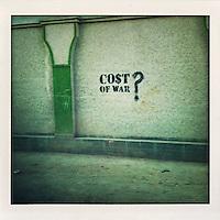 Graffiti written on a Kabul wall reads 'Cost of war?'