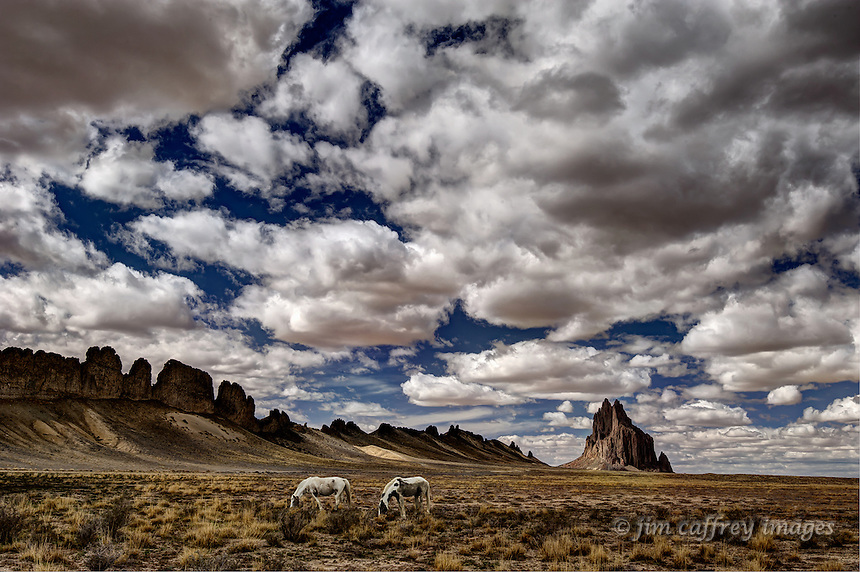 Two horses grazing under a stormy sky with Shiprock in the distance
