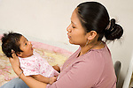 newborn baby girl one month old with mother held interaction horizontal Hispanic Mexican American EVOstock