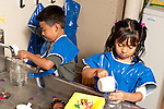 Education preschool 3-4 year olds boy and girl in smocks playing separately at water table