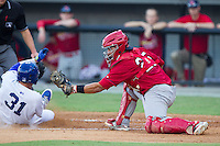 Riley King (31) of the Burlington Royals slides across home plate ahead of the tag attempt by Jose Godoy (25) of the Johnson City Cardinals at Burlington Athletic Park on July 14, 2014 in Burlington, North Carolina.  The Cardinals defeated the Royals 9-4.  (Brian Westerholt/Four Seam Images)