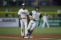 Darryl Collins (23) of the Columbia Fireflies stops at third base as DJ Gladney (8) of the Kannapolis Cannon Ballers looks on at Atrium Health Ballpark on May 19, 2021 in Kannapolis, North Carolina. (Brian Westerholt/Four Seam Images)