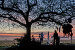 Cowboys are sillhouetted at sunrise as they pour coffee at their campsite in Fazenda Rio Negro, Brazil.