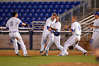 Dunedin Blue Jays outfielder Marcus Knecht #4 is mobbed by teammates Jonathan Jones #25, Gabe Jacobo #8, Andy Burns #9 after game winning hit during a game against the Tampa Yankees on April 11, 2013 at Florida Auto Exchange Stadium in Dunedin, Florida.  Dunedin defeated Tampa 3-2 in 11 innings.  (Mike Janes/Four Seam Images)