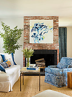 The living room is decorated in blue and white and a brick fireplace is the focal point of the room. A sofa and armchair face each other across a coffee table. A bold piece of modern art is displayed on the chimney breast. The natural flooring and brick give the room texture and warmth.
