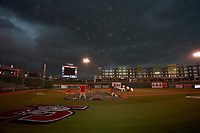 Members of the Lansing Lugnuts grounds crew and team try to keep tarps on the field due to high winds during a weather delay before a game against the West Michigan Whitecaps on August 24, 2021 at Jackson Field in Lansing, Michigan.  (Mike Janes/Four Seam Images)