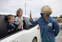 """Jaxon Eley, 6, (from left) and Abigail Eley, 5, of Springdale high-five volunteer Laura Easley, Saturday, April 3, 2021 at Sam's Furniture in Springdale. Samaritan's Feet distributed approximately 720 pairs of shoes to pre-registered students from 18 elementary schools across Springdale in a """"drive-thru"""" event. Each recipient received a """"Hope Tote"""" drawstring book bag that contains a new pair of athletic shoes, socks, hygiene kit and a """"hope note"""" with an encouraging message submitted online from Samaritan's Feet supporters. Check out nwaonline.com/210404Daily/ for today's photo gallery. <br /> (NWA Democrat-Gazette/Charlie Kaijo)"""