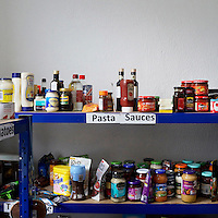 Pasta sauces, condiments and curry sauce line a shelf at the Camden food bank in north London. Volunteers meet customers, offering a hot drink and cake before an interview is carried out to assess the person's need.  After this a specially-selected bags of food are made up.Many food banks are run in or by local churches though not all volunteers at this bank would describe themselves as regular church goers.<br /> <br /> I