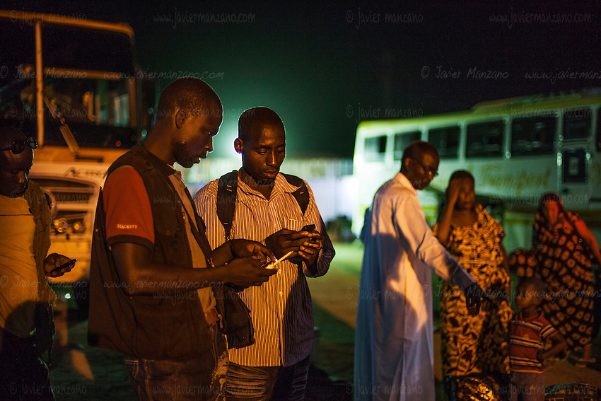 AGADEZ, NIGER — <br /> Two migrants from Burkina Faso exchange telephone numbers upon arriving to Agadez, Niger. This is the final stop of commercial buses. The journey from here on will be through the help of a network of smugglers who drive small pick-up trucks through the Sahara desert on their way to Libya.