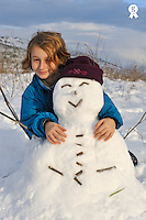 Girl pausing with her snowman (Licence this image exclusively with Getty: http://www.gettyimages.com/detail/89958061 )
