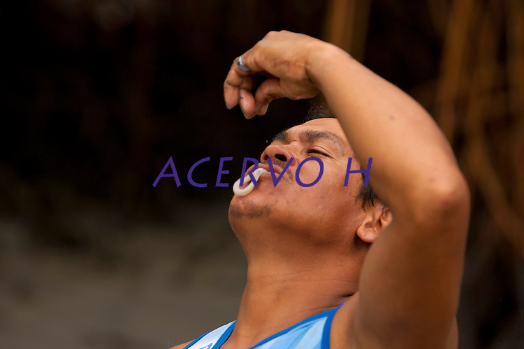 O pescador artesanal  José Alfredo de Souza Costa, 31, conhecido  como Caburé (pássaro da região), enfrenta o período de pesca fraca adentrando o mangue da praia de Paxicú na Reserva Extrativista Marinha Mãe Grande localizada no litoral do Pará, na foz do rio Amazonas, para capturar o turu, (Molusco que habita troncos podres do mangue, também conhecido como bicho-de-pau,. Rico em cálcio e proteína existe a crença nas suas propriedades afrodisíacas).<br /> Curuça, Pará, Brasil<br /> Foto:Paulo Santos<br /> 18/02/2010