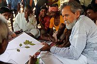 INDIA Chhattisgarh, Prof. Anil Gupta and NGO SRISTI discover on the walking tour Shodh Yatra local knowledge, healing plants and inventions in the tribal villages of Bastar, Gupta and traditional healer / INDIEN Chhattisgarh , Prof. Anil Gupta und sein Team der NGO SRISTI erforschen lokales Wissen, Biodiversitaet, Heilpflanzen und Erfindungen der lokalen Bevoelkerung auf der Shodh Yatra einer Wandertour durch Adivasi Doerfer in der Bastar Region, Medizinmann des Dorfes erklaert Nutzung der Heilpflanzen
