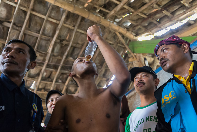 """5 April 2017, Surabaya,East Java,Indonesia: Febrianto, a 24 year old mental illness sufferer takes a drink after his release from the chains he has been shackled to a stake for the past two years in a goat shed next to his family in Pehwetan village, East Java. His mother Barokah, looks on as Indonesian Social Affairs Dept. workers cut the bonds and wash his emaciated body and apply first aid before putting him in a straight jacket and taking him to a facility in Malang for treatment. Febrianto is a patient in a program called """"E- Shackling"""" which aims to free people suffering from mental illness, from the shackles that family often place them in to control them in the wake of a lack of treatment options and which will treat them and enter them in a data base allowing them to be traced before releasing them back to their families. Some people stay chained to a stake or in rooms for years by their families and not all families are willing to take their sick family members back. Picture by Graham Crouch/The Australian"""