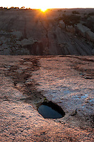 """Enchanted Rock sunset with runoff.  Taken just as the sun drops over the """"Little Rock"""" to the west of the main dome one spring evening."""
