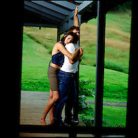 Couple standing on porch embracing seen through screen door