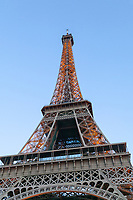 The Eiffel Tower with its lights beginning to show in early evening, Paris, France