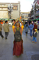 Prostration in Tibetis an important expression of devotion to Tibetan Buddhism. Prostrating is practicing one of Buddhism's three Jewels for Tibetan Buddhists. Tibetan pilgrims prostrate themselves by lying face-down on the ground and stretching out their arms and legs so as to earn merit.<br /> <br /> Tibetan pilgrims always perform prostrations before monasteries in Tibet and before sacred images displayed on altars or when they enter and withdraw from a room. Some pilgrims from distant places in Tibet even prostrate themselves to their pilgrimage destination, like Lhasa and Mountain Kailash. They would spent several years making pilgrimages to Lhasa and other religious centers, covering the entire distance in a series of prostrations. Tibetan Buddhists also prostrate before their teachers.<br /> Tibetans ideally are expected to prostrate themselves 100,000 times a year, which works out to almost 300 times a day, every day of the year. Not only do they prostrate themselves around temples they also do it on roads, streets and sidewalks. Some pilgrims cover the entire 33-mile route around Mount Kailash or travel from their hometowns to Lhasa, repeatedly prostrating themselves.
