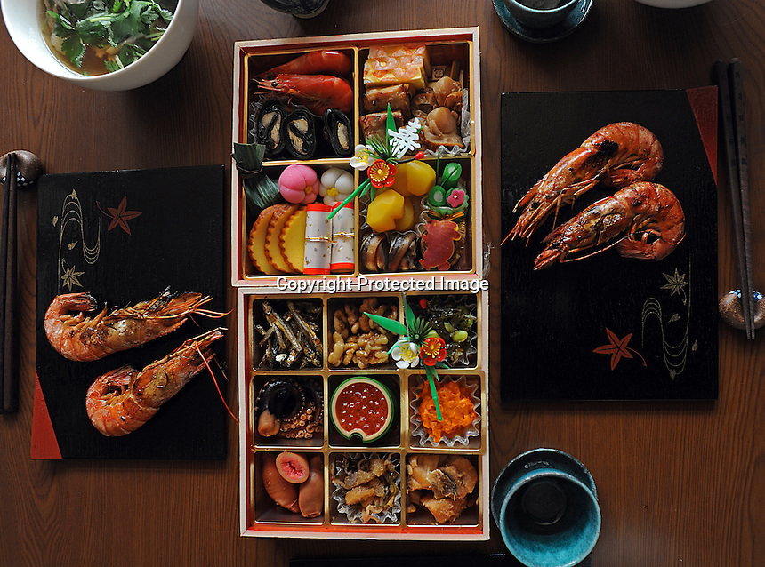 New Year food, azukuri (dried fish),  kazunoko (herring egg), datemaki (egg roll)  Kurikinton (chessnuts in sweet potato paste), Kobumaki (seaweed fish roll), Ebiyaki (Grilled prawn) - curled up prawn represents long life, Nishime (stewed vegetables)  in a residential area in Tokyo, Japan.  The Japanese celebrate the first three days of the New Year which are public holidays and days of rest of visits to shrines and good food.