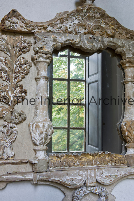 An 18th century window is reflected in a small mirror within a carved wood frame