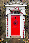 England. Red door in white Georgian frame with red Christmas berries wreath and decorations.
