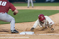 Arkansas Razorbacks infielder Bobby Wernes (7) dives back to first base at Baum Stadium during the NCAA baseball game against the Alabama Crimson Tide on March 21, 2014 in Fayetteville, Arkansas.  The Alabama Crimson Tide defeated the Arkansas Razorbacks 17-9.  (William Purnell/Four Seam Images)