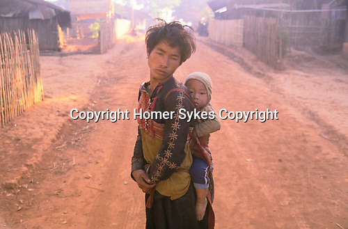 Opium addict with child his son Hmong village Northern Thailand South East Asia Chiang Rai province.  1990s
