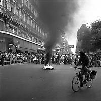 """Carrefour de l'avenue d'Alsace-Lorraine et de la rue Lafayette. 5 septembre 1975. Scène de manifestation : au 1er plan feu et fumée noire (pneus) au milieu de la route, un cycliste passe devant et regarde le feu ; au 2nd plan une rangée de personnes bloque la circulation, foule sur le trottoir ; en arrière-plan perspective de l'avenue d'Alsace-Lorraine, façades, commerce """"Printafix"""", bus. Cliché pris lors d'une manifestation contre le Général Franco."""