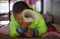 A visually impaired Tibetan student plays with a braille book at the boys' dormitory of the School for the Blind in Tibet, in the capital city of Lhasa, September 2016.