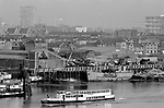 River Thames at Wapping, East London 1980s UK. Passenger ferry riverside industry, boatyards 1987. St Paul's Church Shadwell on horizon. 80s England