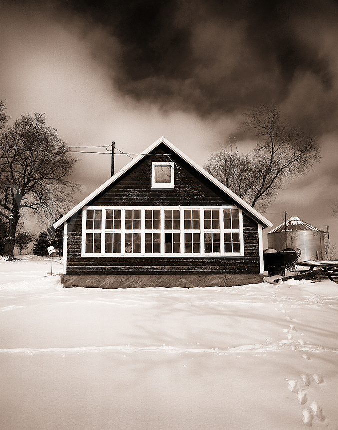 The exterior facade of a house with a snowy yard.
