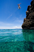 A young woman jumps off Black Rock, Ka'anapali, Maui.