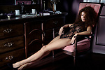 Artistic sensual boudoir portrait of a sexy beautiful woman sitting in a chair by a dresser in underwear with a piercing glaring look and stretched long legs. Vintage retro French style. Image © MaximImages, License at https://www.maximimages.com