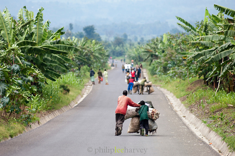 Father and son pushing loaded cart down a long road in Rwanda