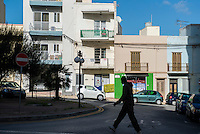 Malta, Bugibba, Northern region of Malta.<br /> <br /> In the winter a quiet tourist area with mainly older overwintering English tourists.  Many places are closed and lots of appartments are boarded up.<br /> Tourist enjoying the winter sun and a smoke at her balcony.<br /> <br /> Photo Kees Metselaar