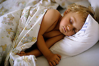 Two year old girl asleep in bed, France.