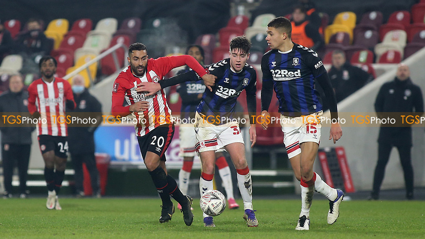 Saman Ghoddos of Brentford and Middlesbrough's Hayden Hackney look on as Nathan Wood of Middlesbrough gets ready to pass the ball upfield during Brentford vs Middlesbrough, Emirates FA Cup Football at the Brentford Community Stadium on 9th January 2021