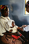 Mbati, Zambia. Woman with her baby daughter receiving an innoculation injection at a rural medical post.
