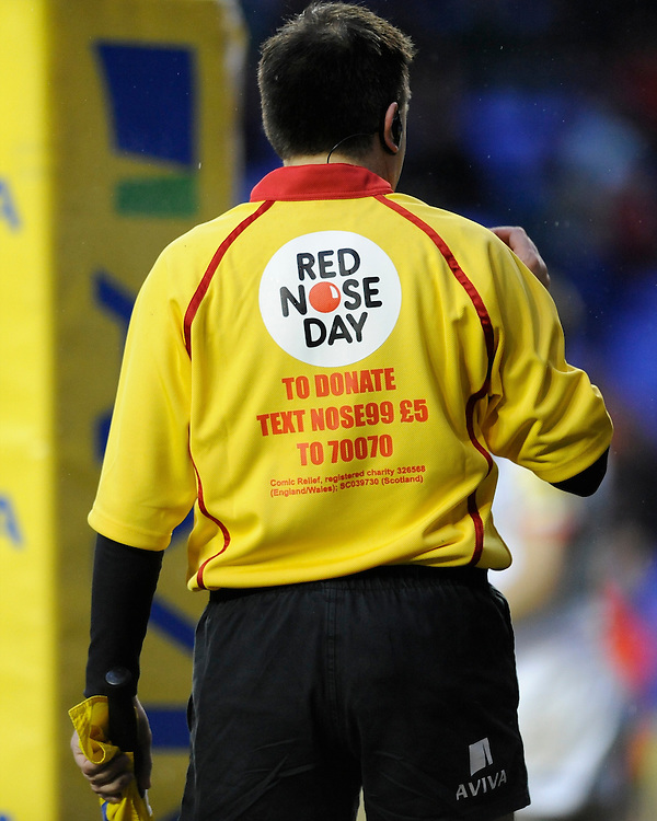 Comic Relief branding on the assistant referee's shirt during the Aviva Premiership match between London Irish and Saracens at the Madejski Stadium on Saturday 9th February 2013 (Photo by Rob Munro)