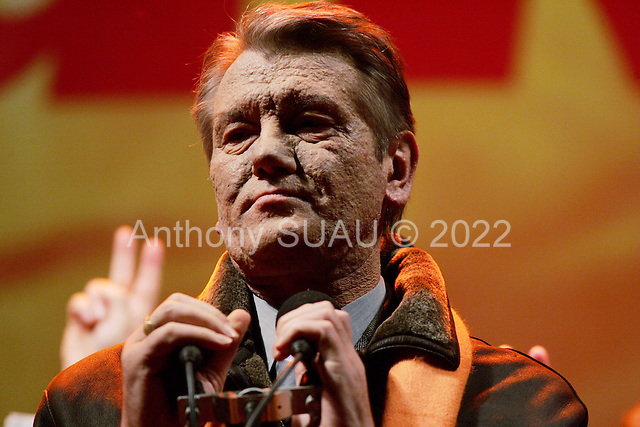 """Kiev, Ukraine.December 28, 2004..Opposition candidate Viktor Yushchenko takes center stage on Maidan Independence Square as thousands of Orange flag waving supporters rally to his side. Election polls show him as a clear winner however he has not yet been declared the winner nor has his opponent refuses to admit defeat...He is joined on stage by his wife Kathy, his son Andrey and his political partner Yulia Timoshenko. ..The first round of voting was considered fraudulent when the ruling president Viktor Yahukovich won and the opposition candidate Viktor Yushchenko lost. ..Several hundred thousand Ukrainians took to the streets of Kiev and held daily rallies on Maidan Independence Square. The protests lasted nearly a month before the first vote was declared invalid and a new round of elections held on December 26, 2004. ..The demonstrations would come to be known as the """"Orange Revolution"""" after the color of the opposition party."""