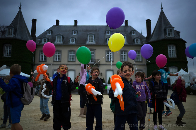 Children with balloons dance in front of the castle of the Domaine Solvay, in La Hulpe, Belgium on April 19, 2013. The castle is managed by the Walloon Regional government, but it is visited by school groups from both language communities.
