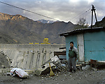 Elderly man, Abay, 68, stands near a house guard. He works as a janitor, he sweeps debris from the asphalt, which allowed drivers staying on the observation deck, which would look at Kambarata HPP. Kyrgyzstan. 2012