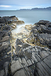 Rocky shoreline dominated by barnacles, looking north to the Ardnamurchan Peninsula. Glengorm Estate, north west coast, Isle of Mull, Scotland. June
